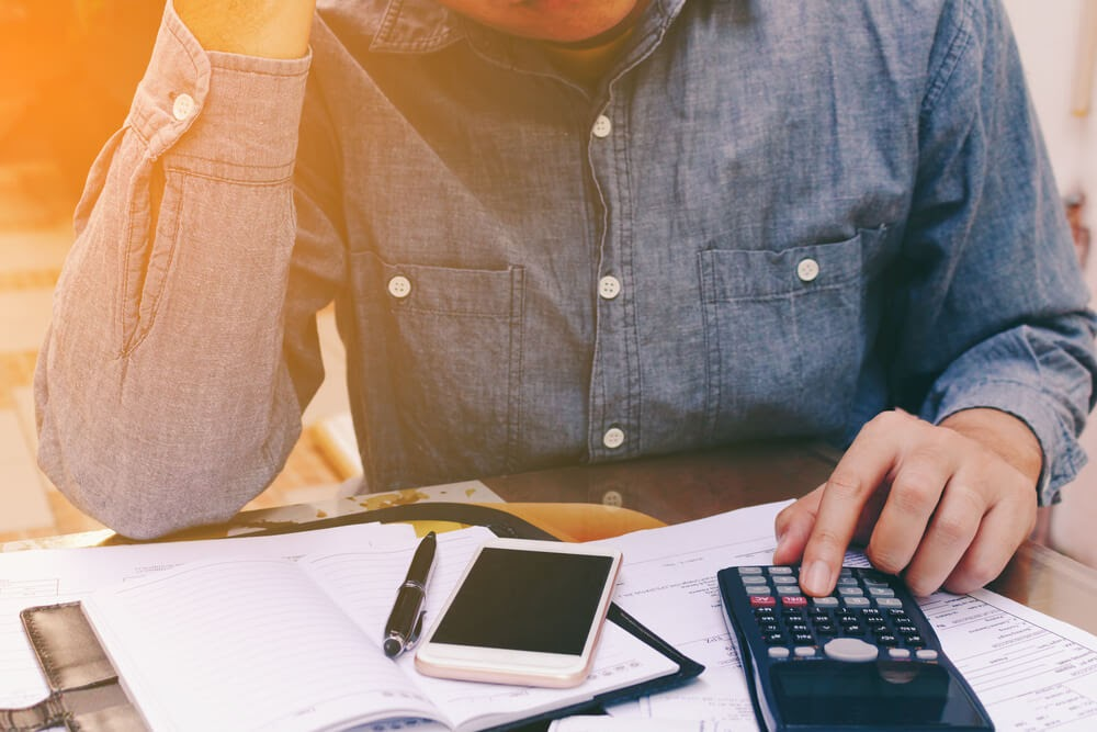 Man looking over his finances with his calculator