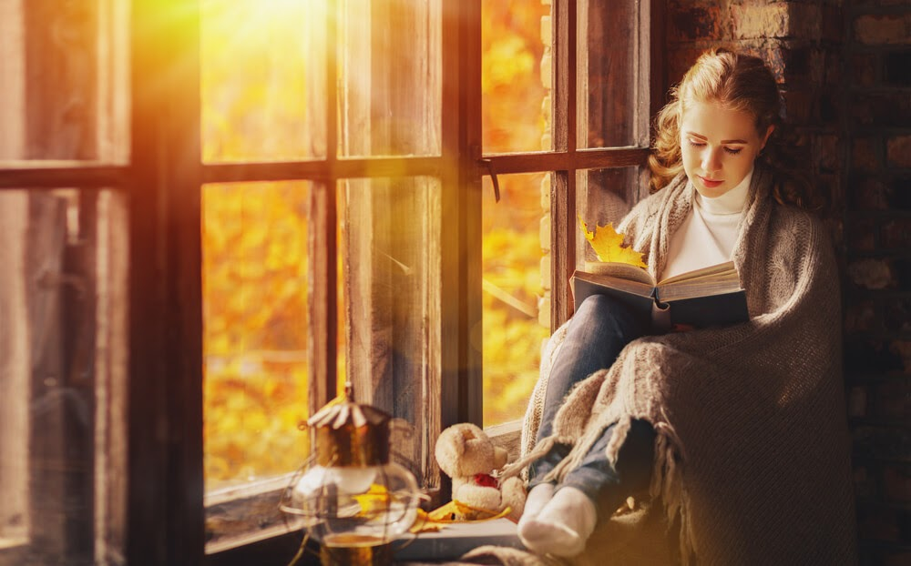 Woman reading a book in a window seat
