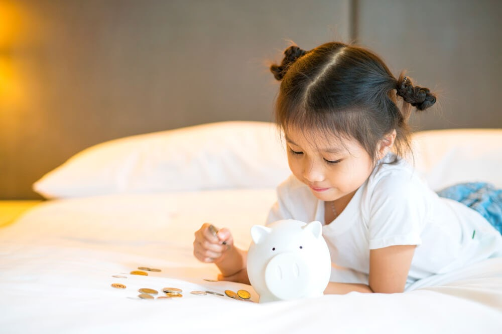 Girl counting her pennies in her piggy bank