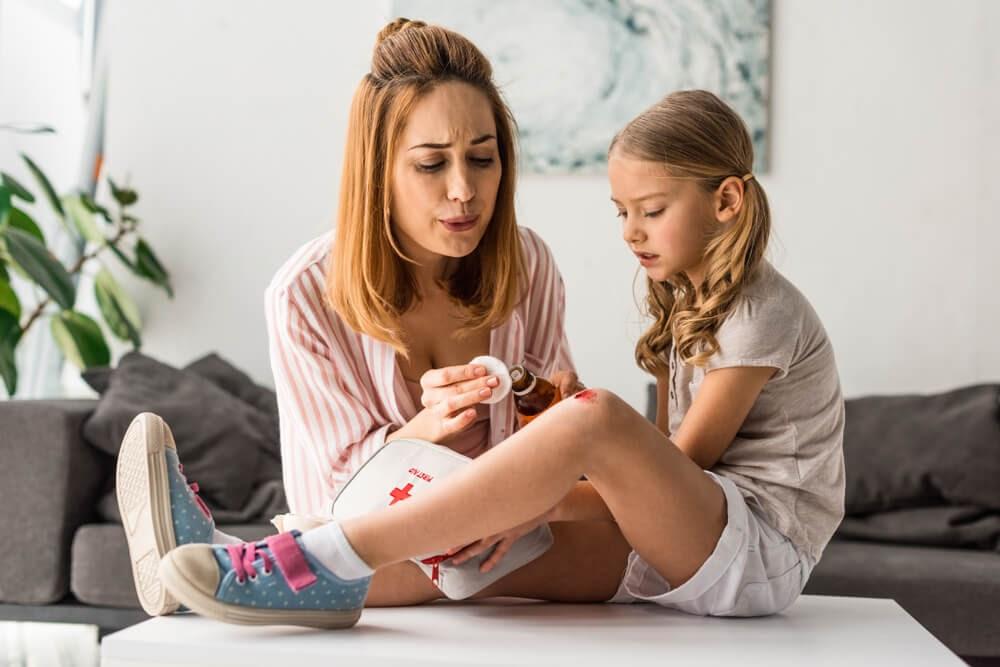 Mom looking at daughter's scraped kneei