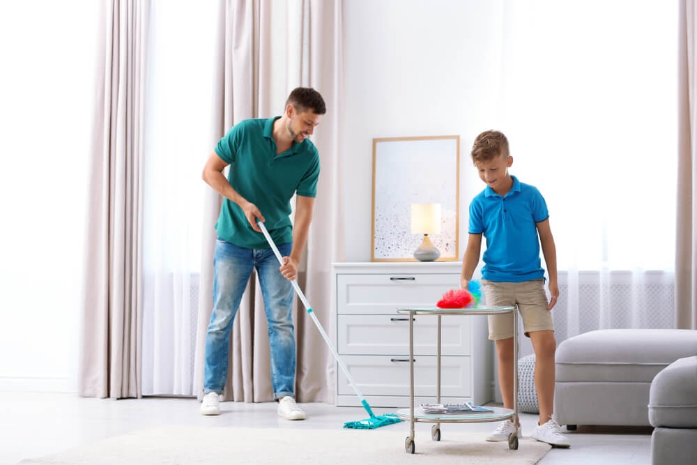Father and son dusting the living room together