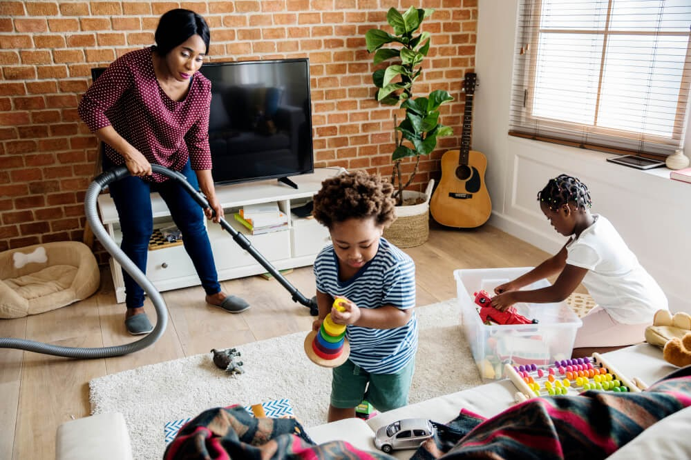 Mom vacuuming while children play