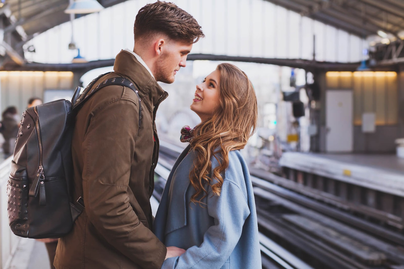 Man and woman looking longingly into each other's eyes at a train station