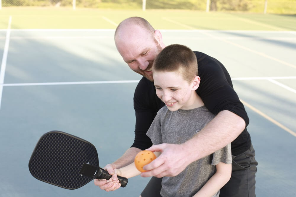 Dad teaching his son how to play pickleball