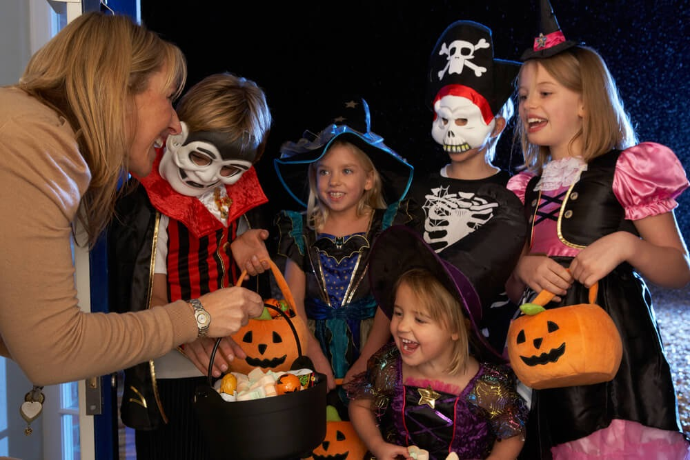 Woman handing out candy to group of trick or treaters