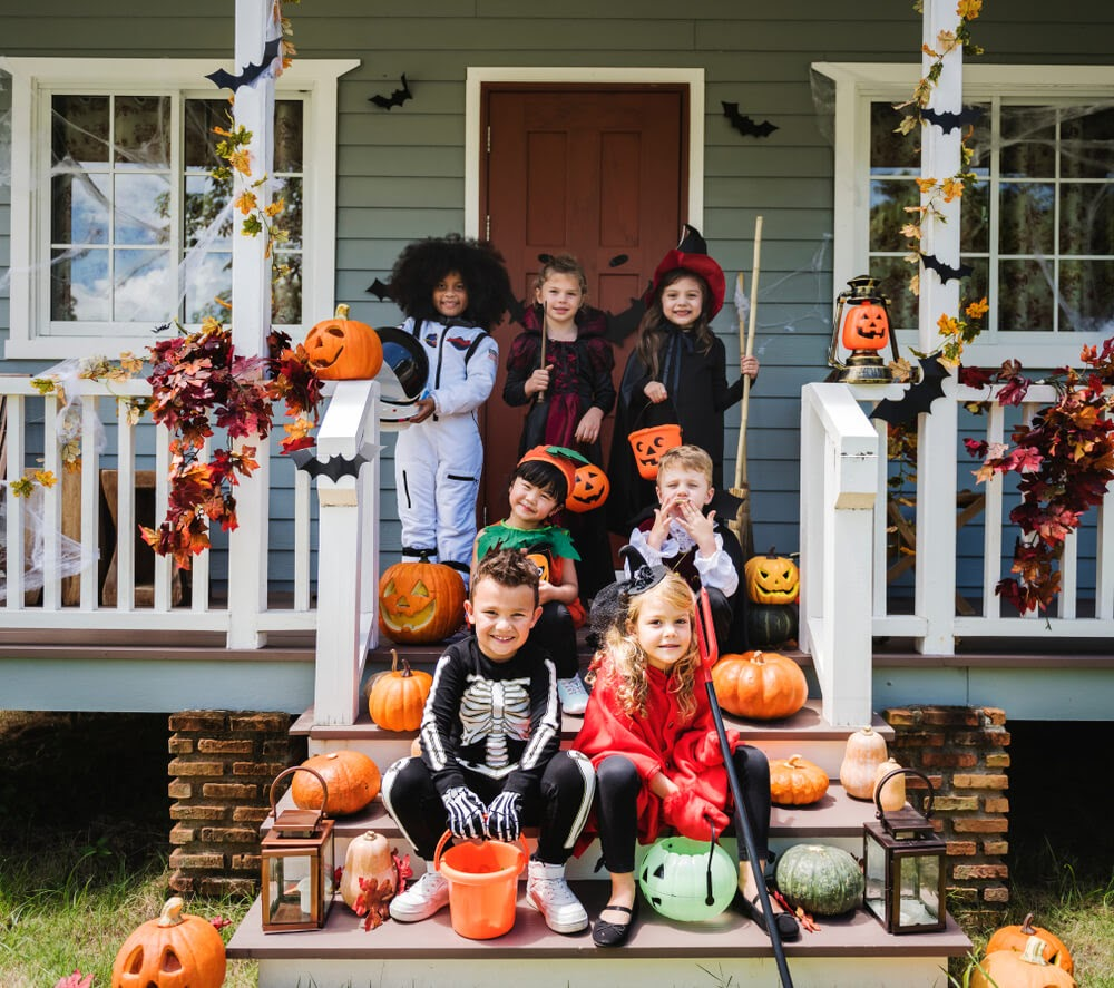 Group of children on the front porch dressed up in costume
