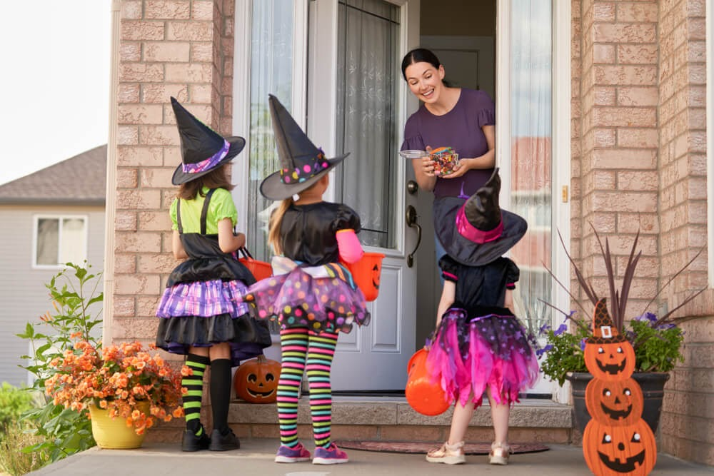 Woman with a bag of candy and three girls dressed up as witches at her door