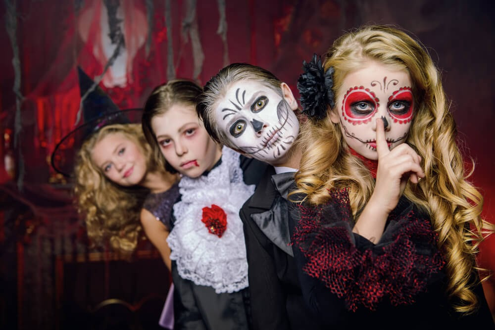 Children in halloween costumes looking at the camera