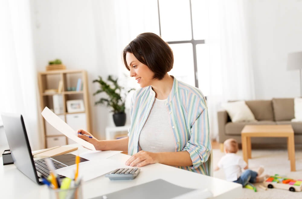 Woman looking over her financial statements in front of a laptop