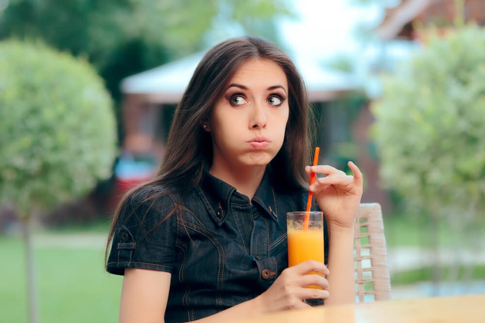 Woman looking uncertain after she takes a drink of orange juice