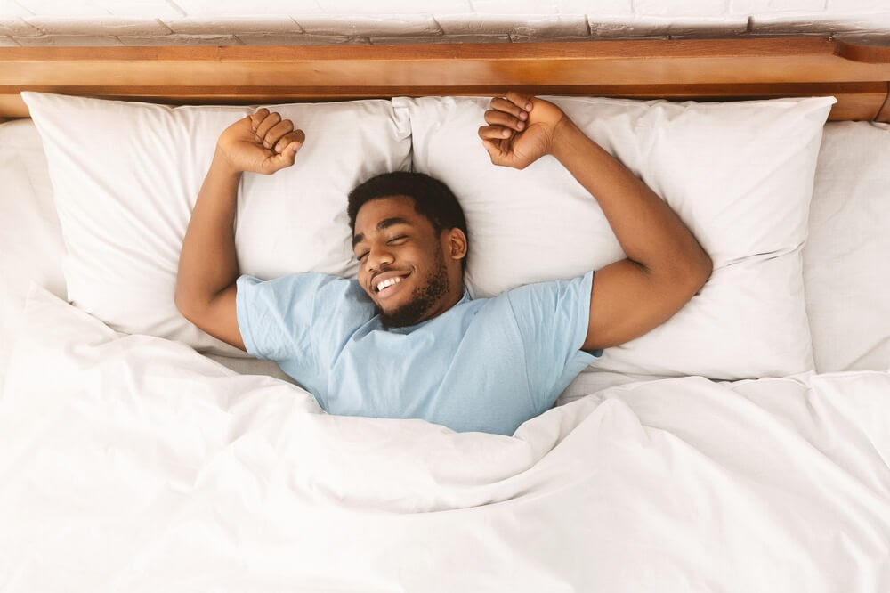 Man stretching in bed after a good night sleep