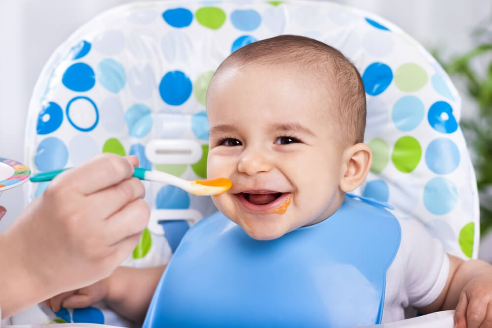 Baby boy smiling in high chair while he eats