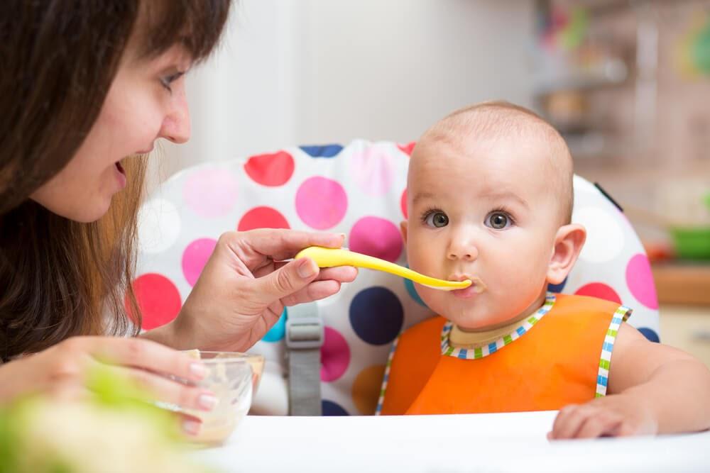 Mom feeding green eyed baby girl