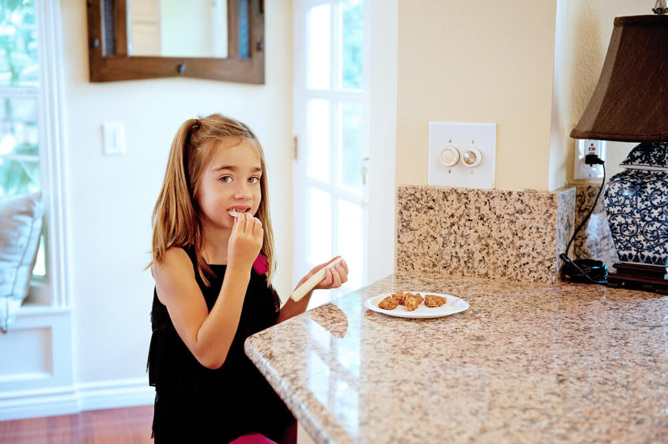 Girl eating some snacks at the kitchen counter