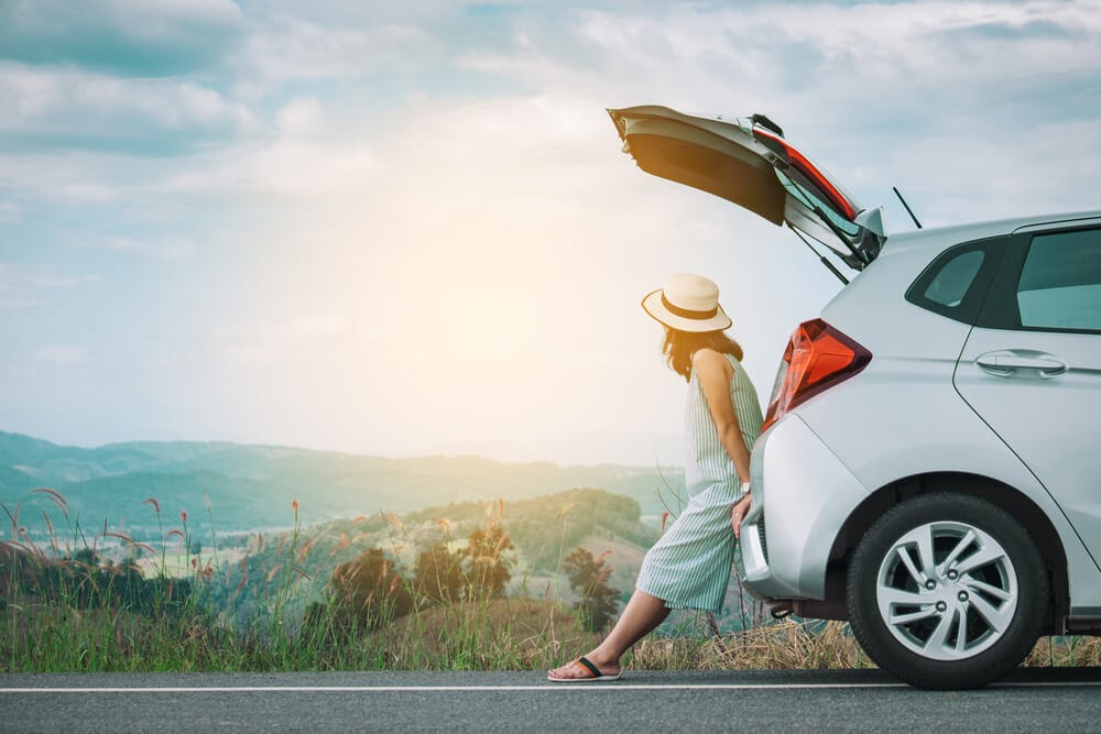 Woman looking at the scenery from the back of her car