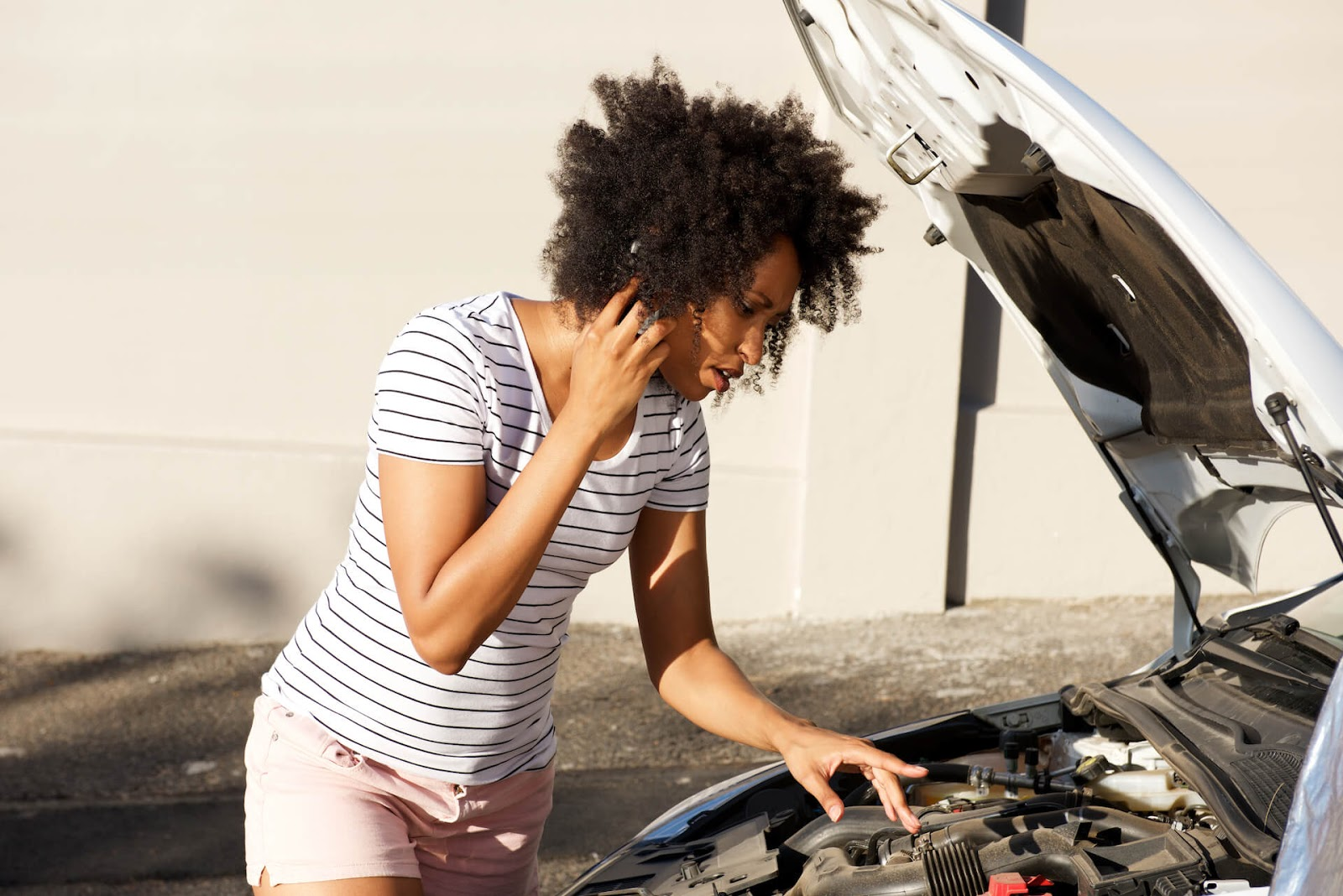 Woman on the side of the road looking at her engine