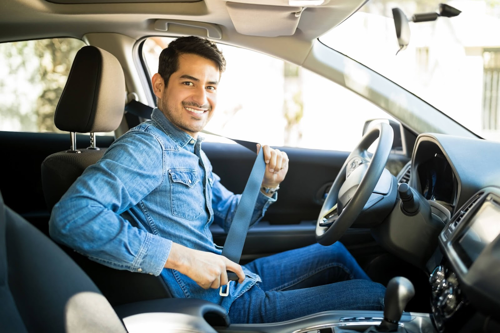 Man smiling at the camera while he puts on his seatbelt