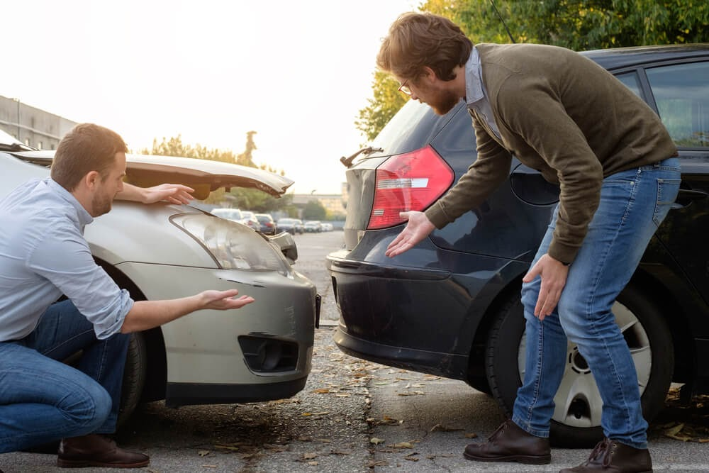 Two men looking at their cars after a rear-end accident