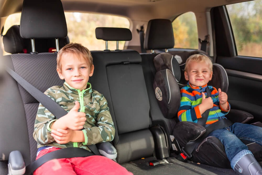 Two brothers giving a thumbs up to the camera from their booster seats