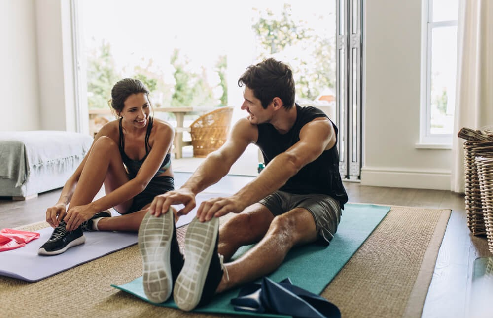 Man and woman stretching on their yoga mats