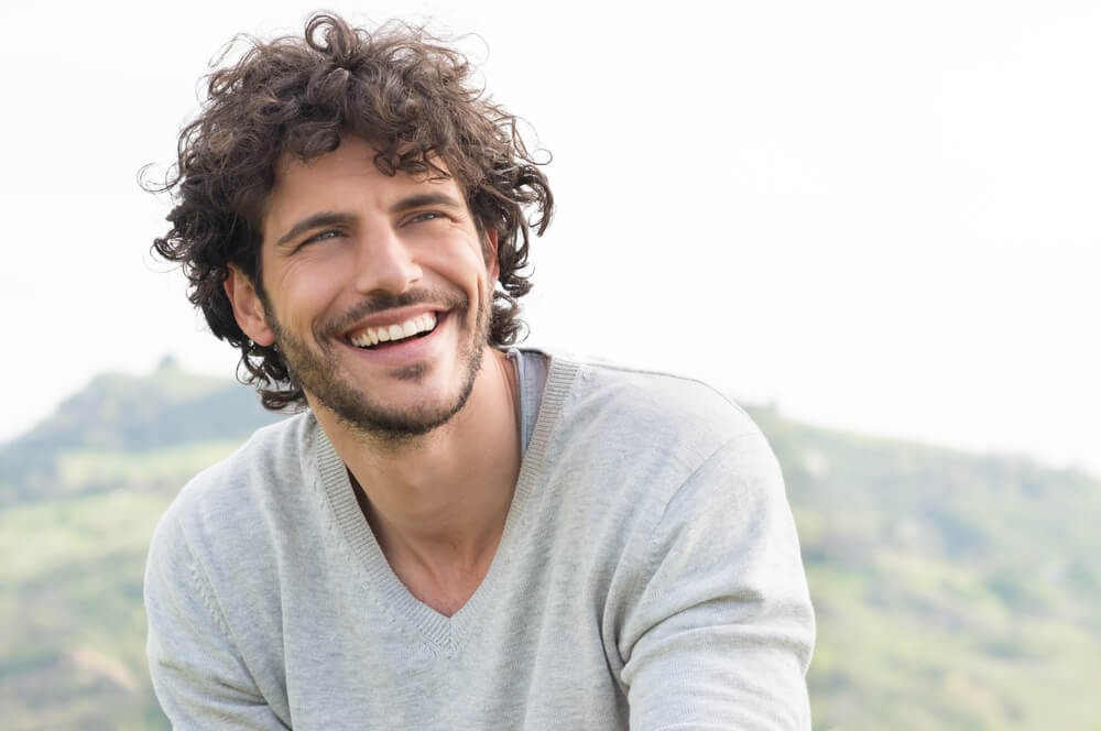 Man smiling with a hill in the background