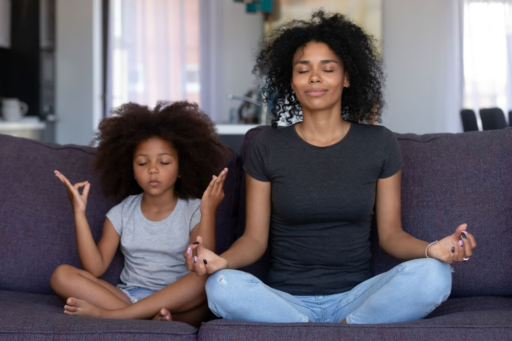 Mom and daughter meditating