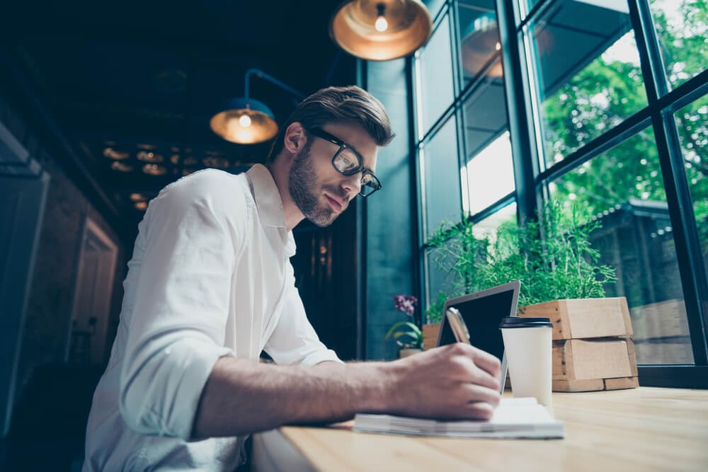 Man writing in a notebook at a coffee shop