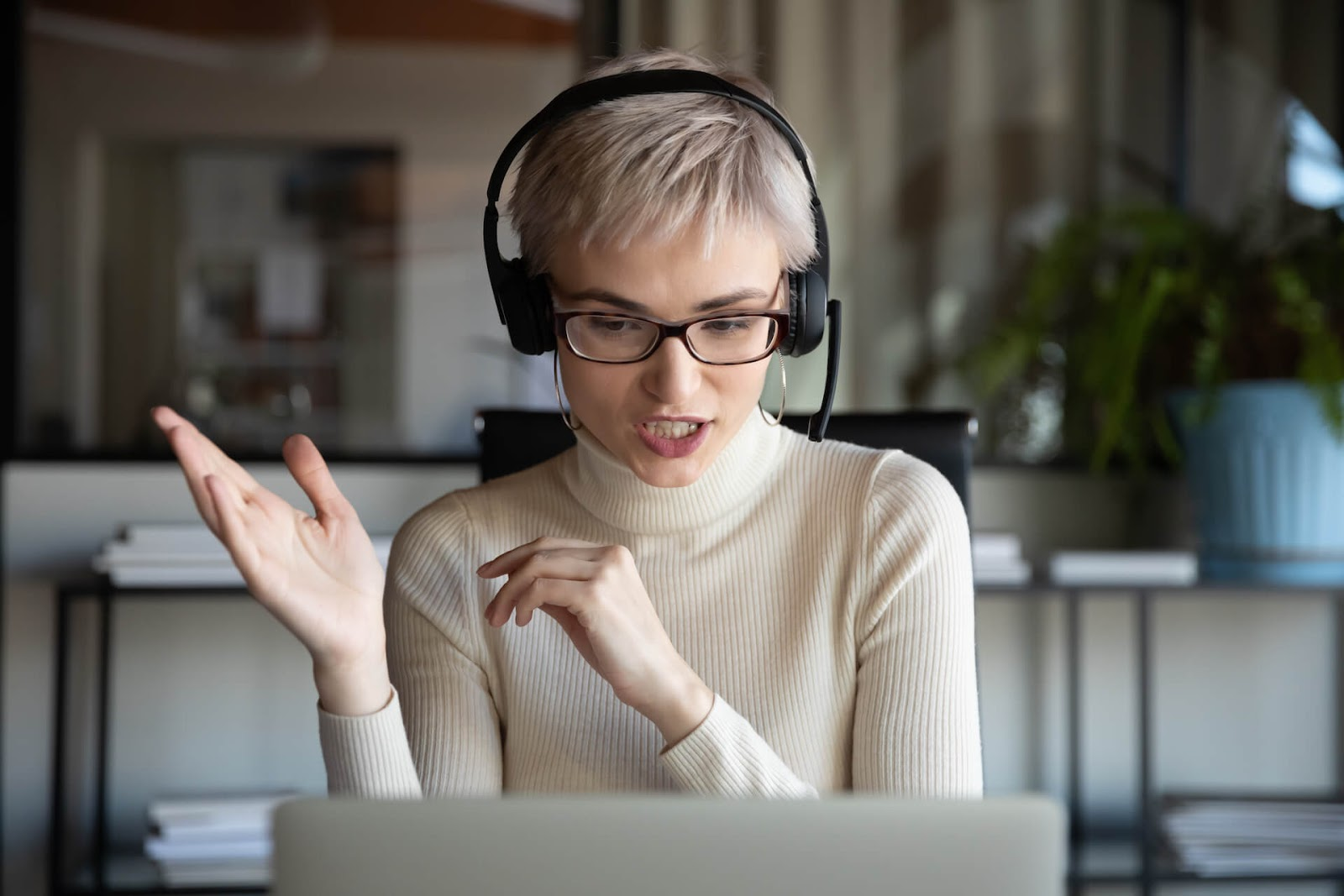 Woman recording a podcast on her laptop