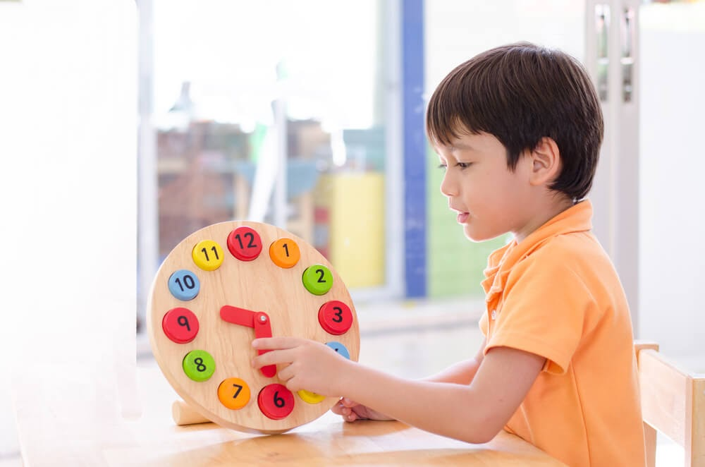 Young boy playing with wooden clock