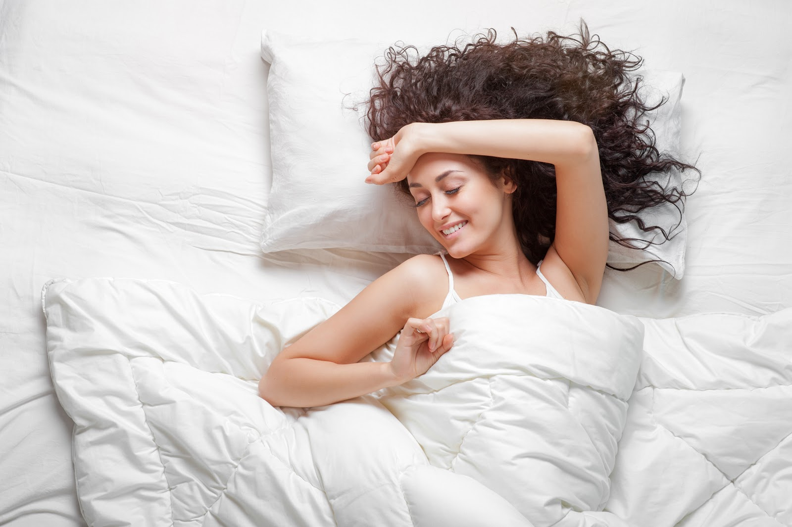 Woman stretching out in bed