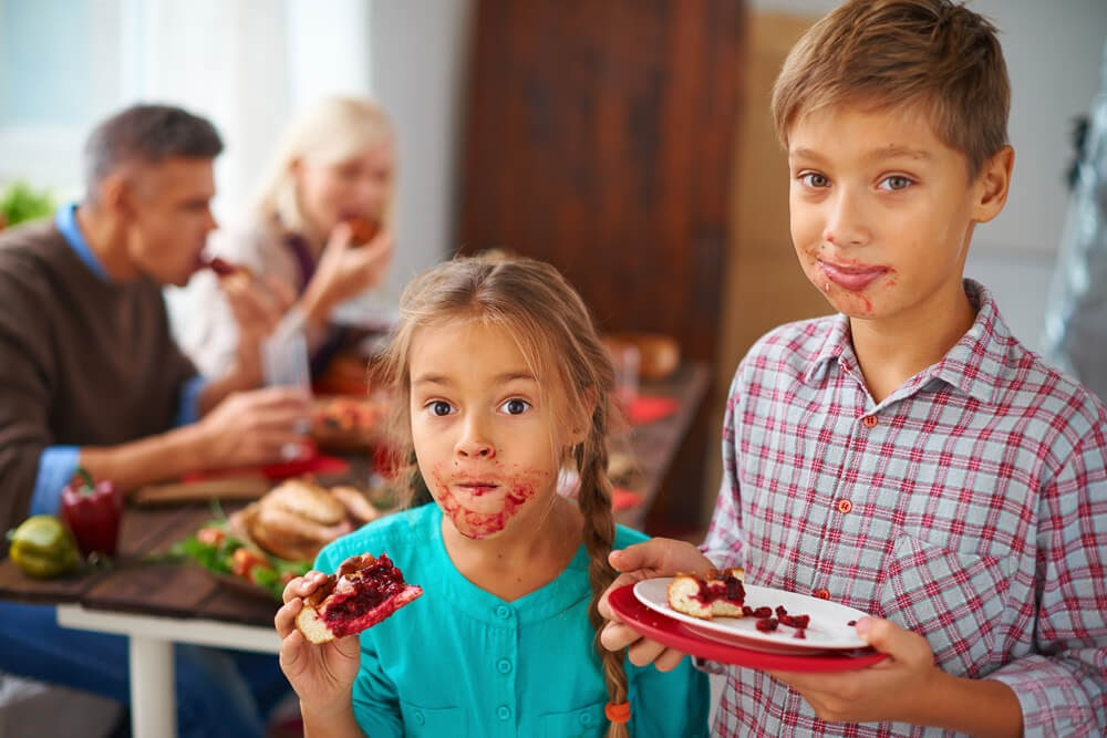 Kids enjoying thanksgiving meal with messy faces
