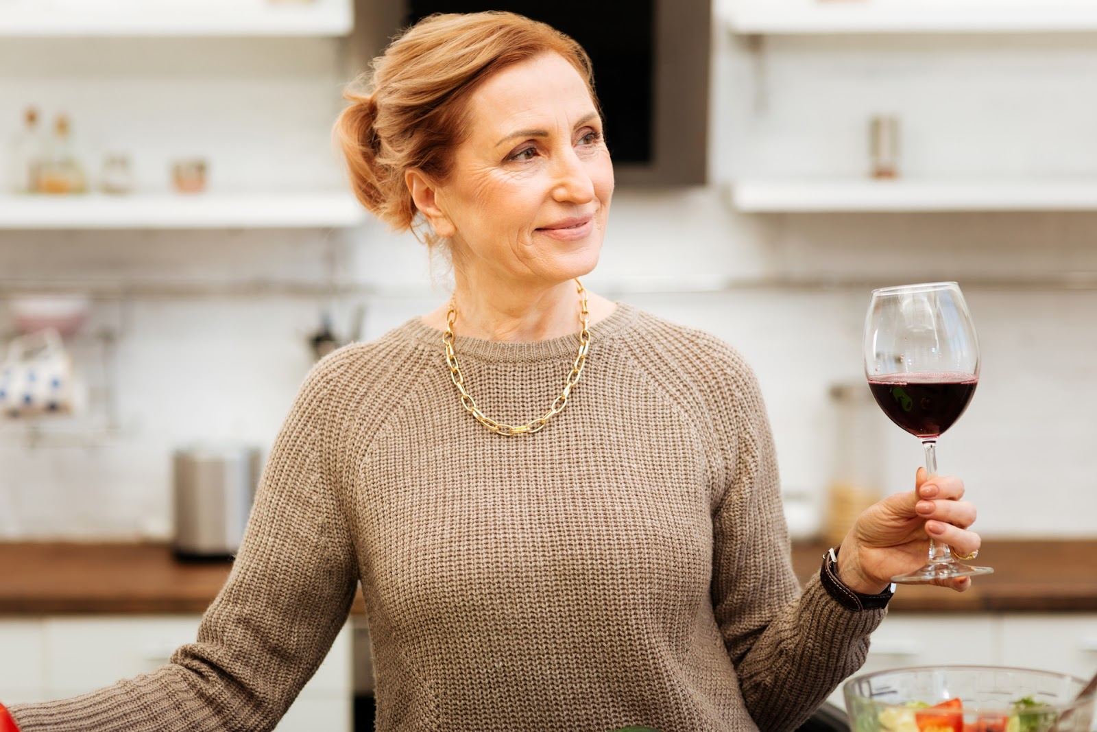 Woman drinking a glass of wine in her kitchen