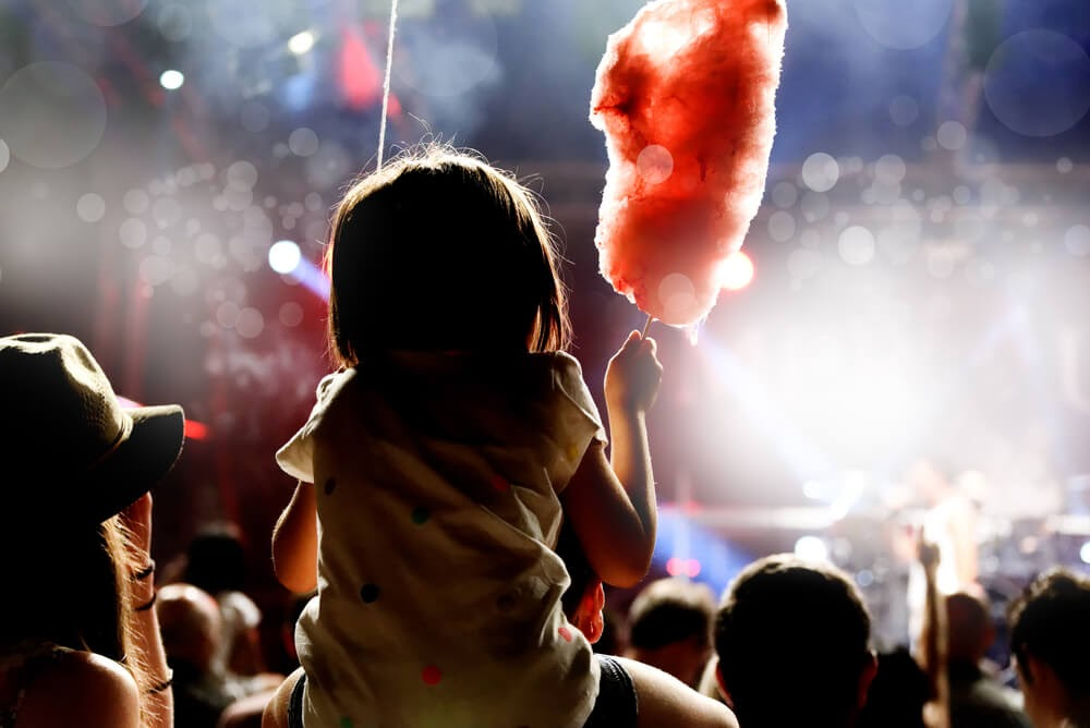 Little girl eating cotton candy on her dad's shoulder at a concert