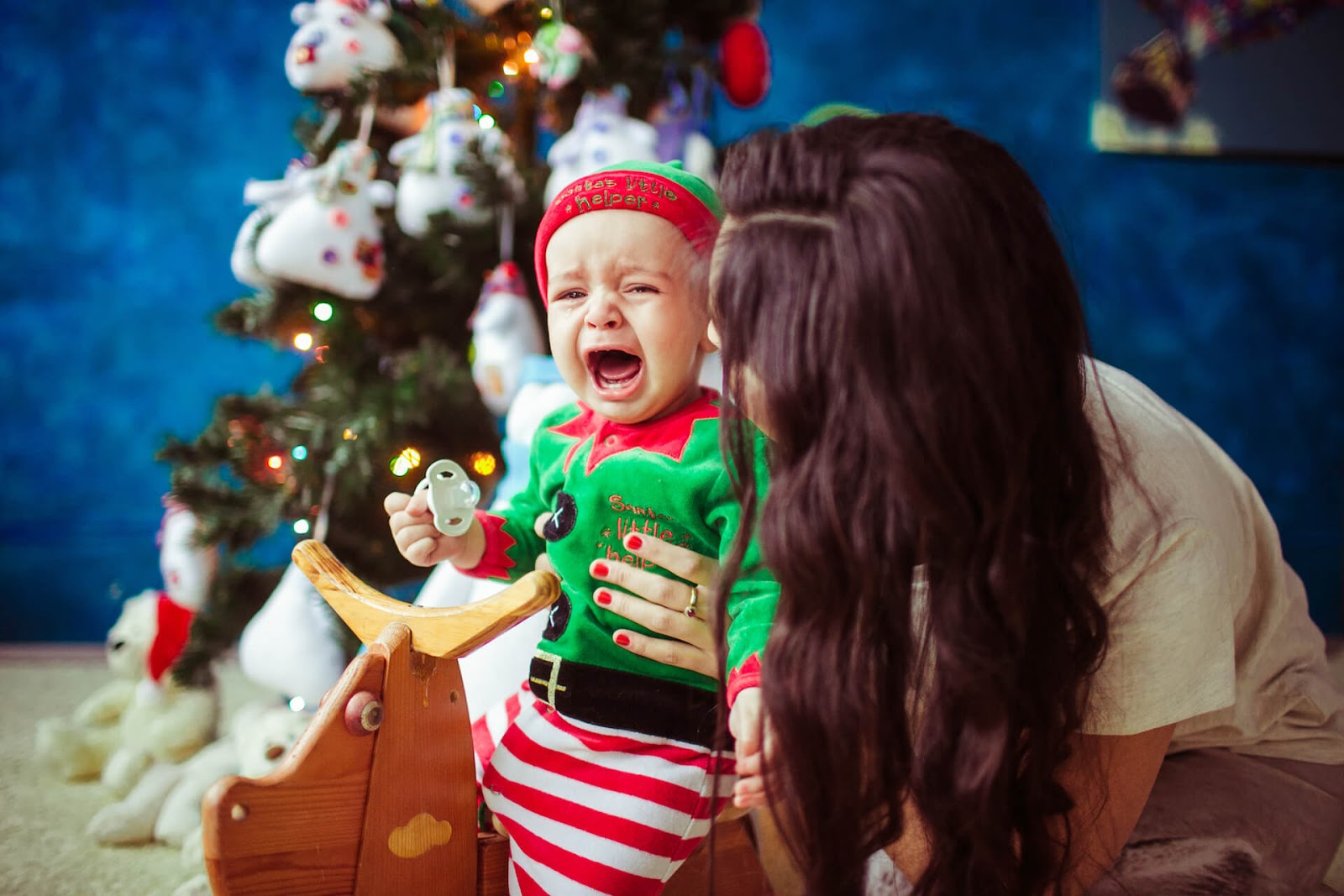 Baby crying in front of Christmas tree