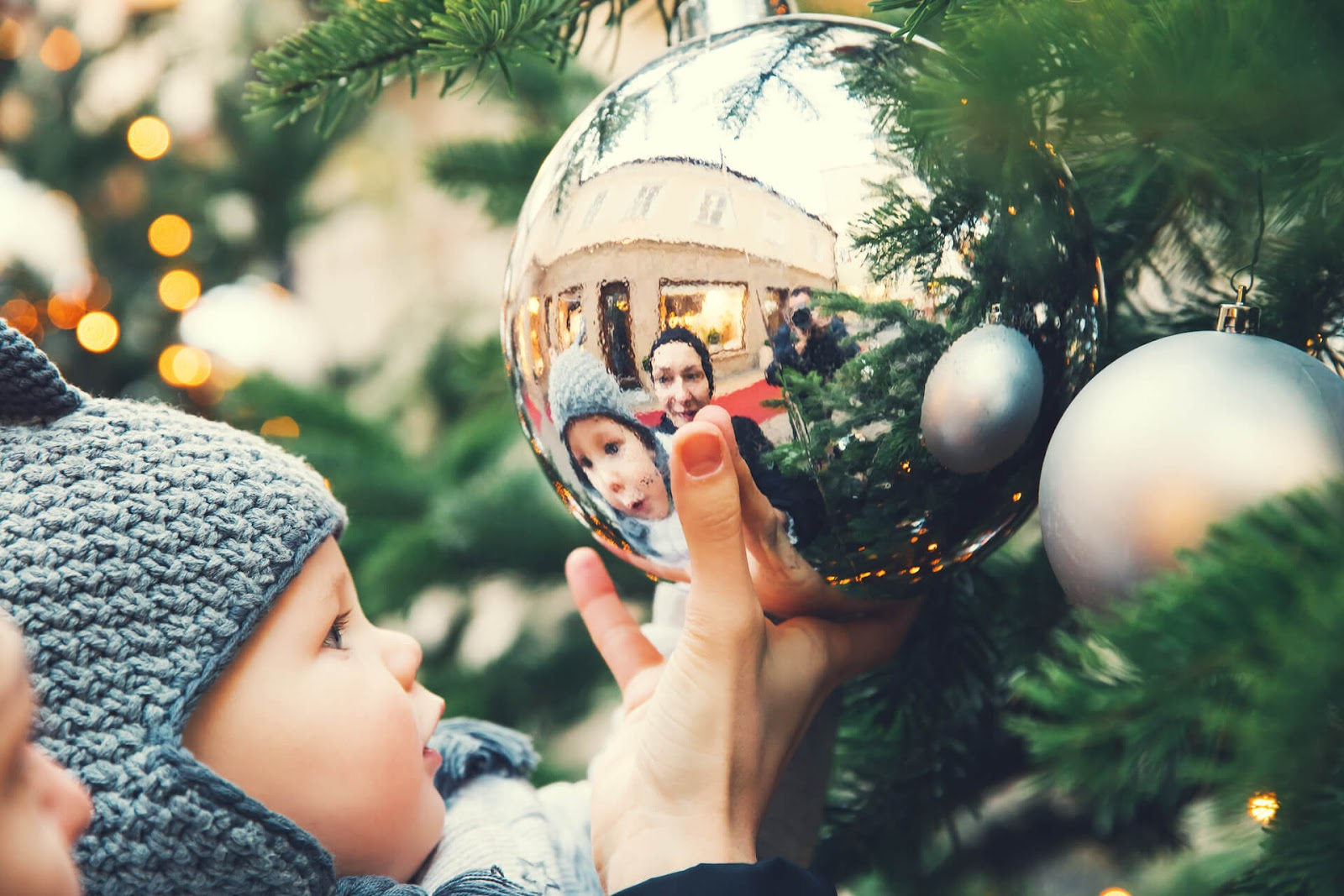 Baby looking at giant ornament on Christmas tree