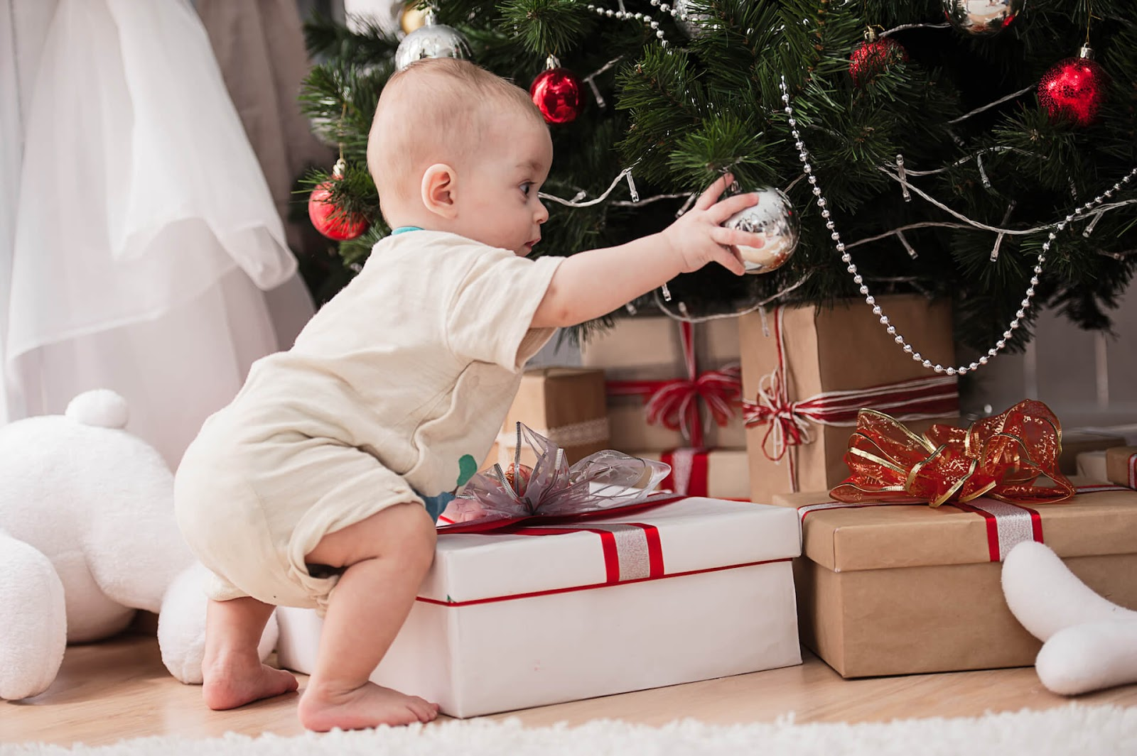 Baby playing with ornament on Christmas tree