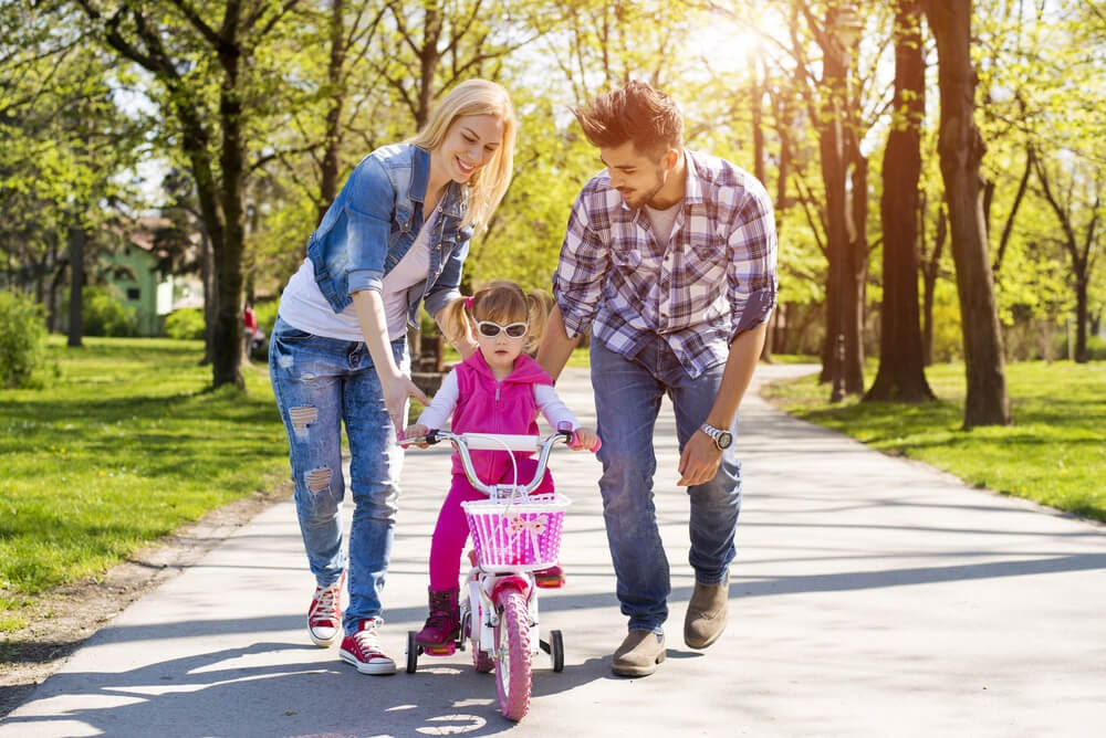 Parents teaching daughter to ride a bike in a pk