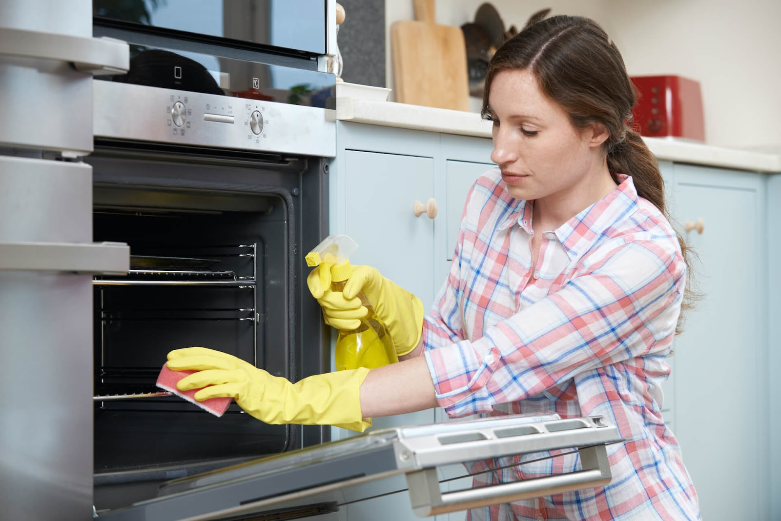 woman scrubbing her oven
