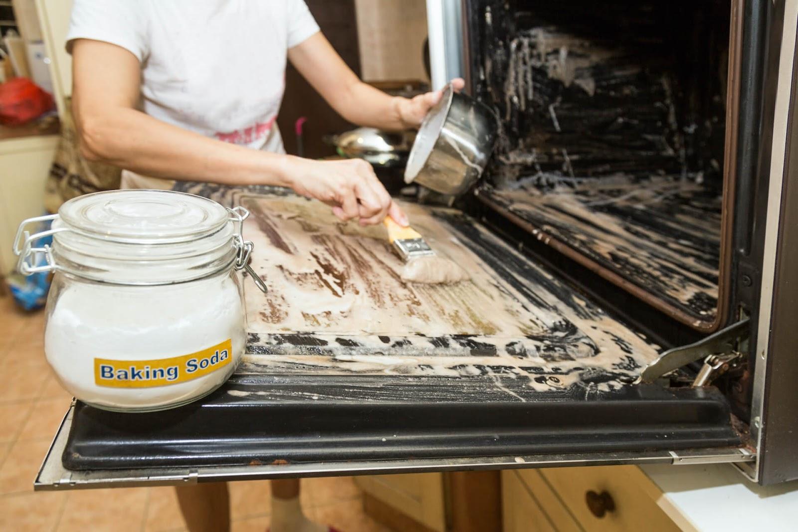 Woman scrubbing baking soda on her oven
