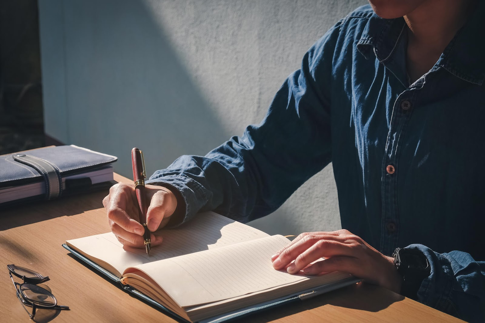 Man writing in journal at desk