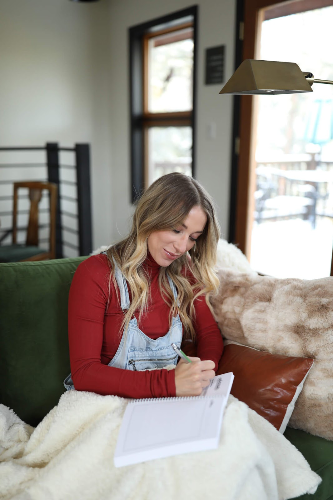 Woman writing in a journal on the couch