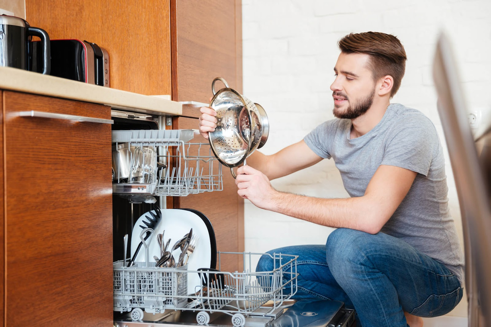 Man looking at dishes in his dishwasher