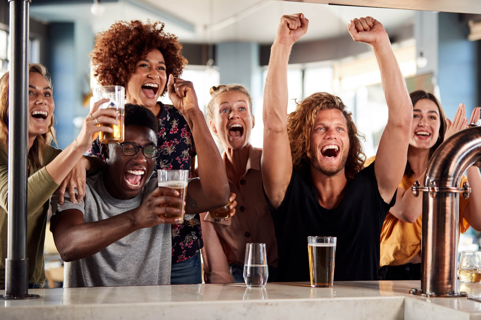 Group of people cheering at a spots bar