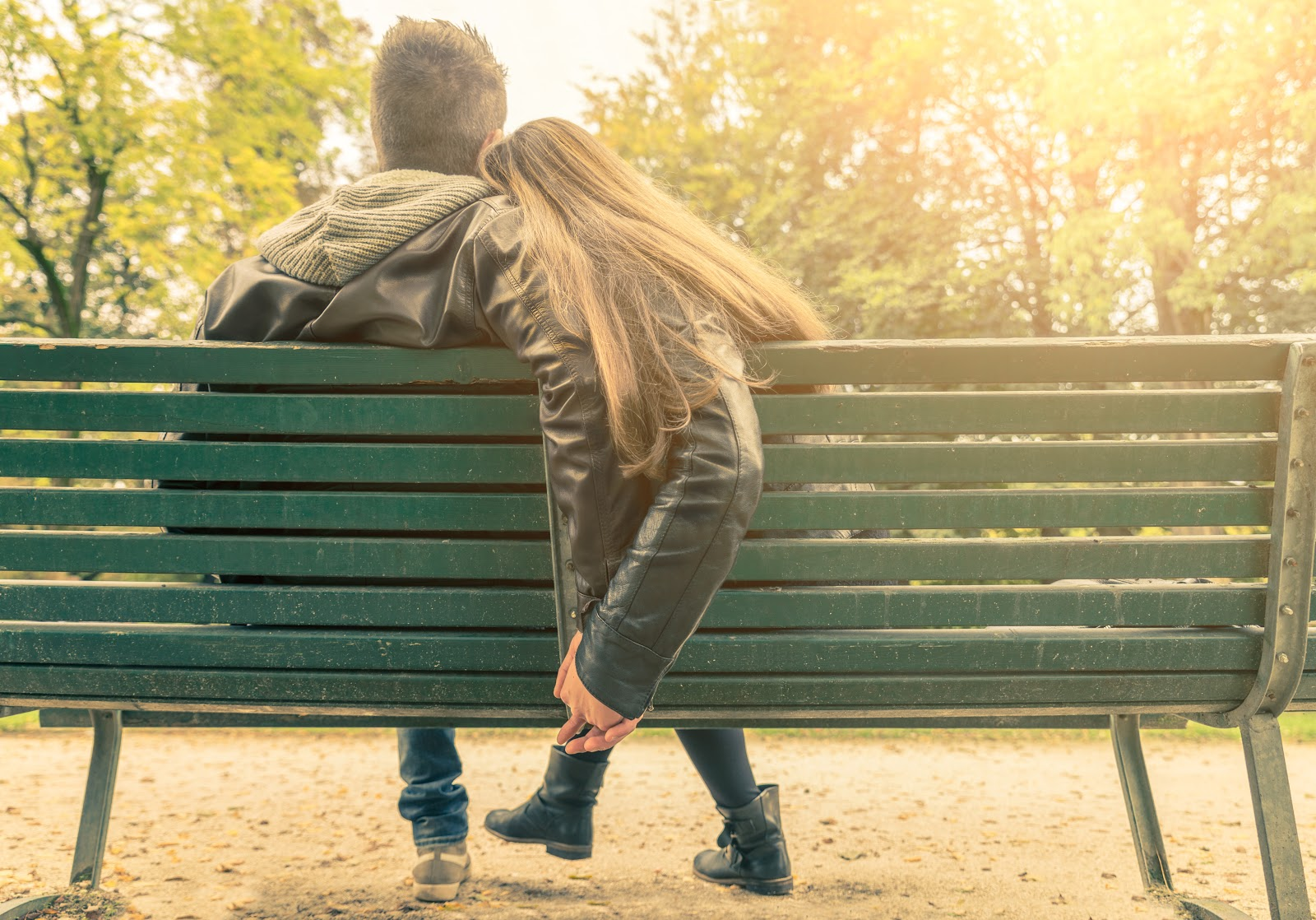 Woman and man cuddling on a park bench