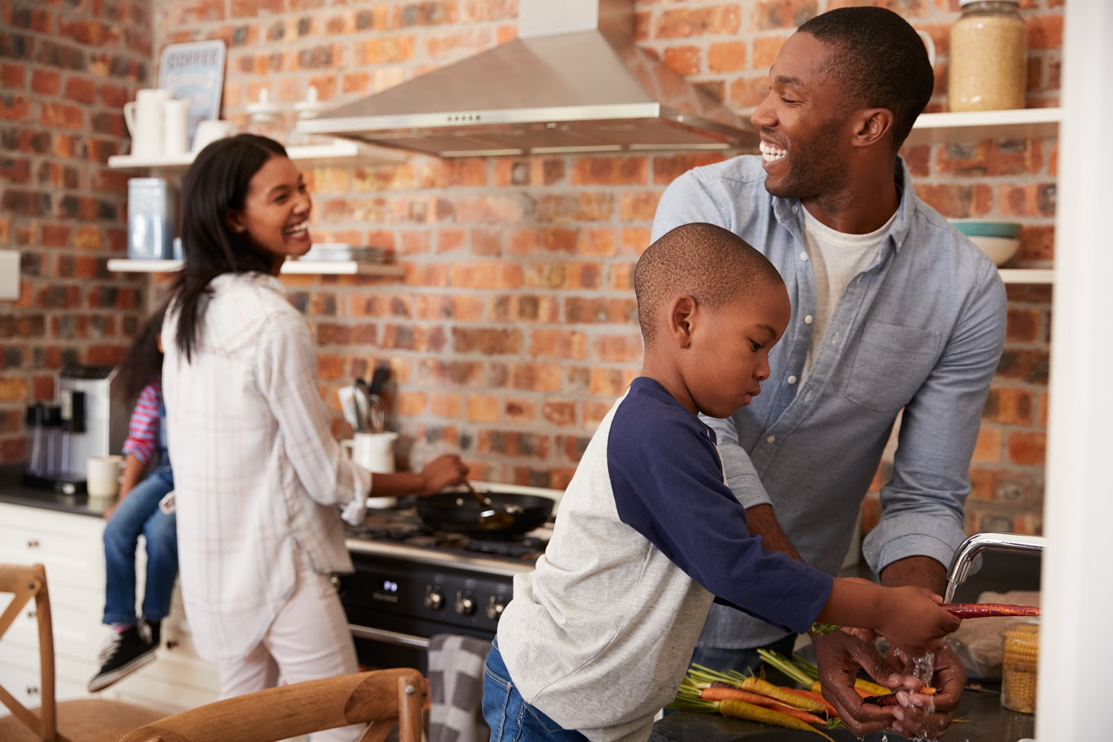 Family cooking in the kitchen together and laughing