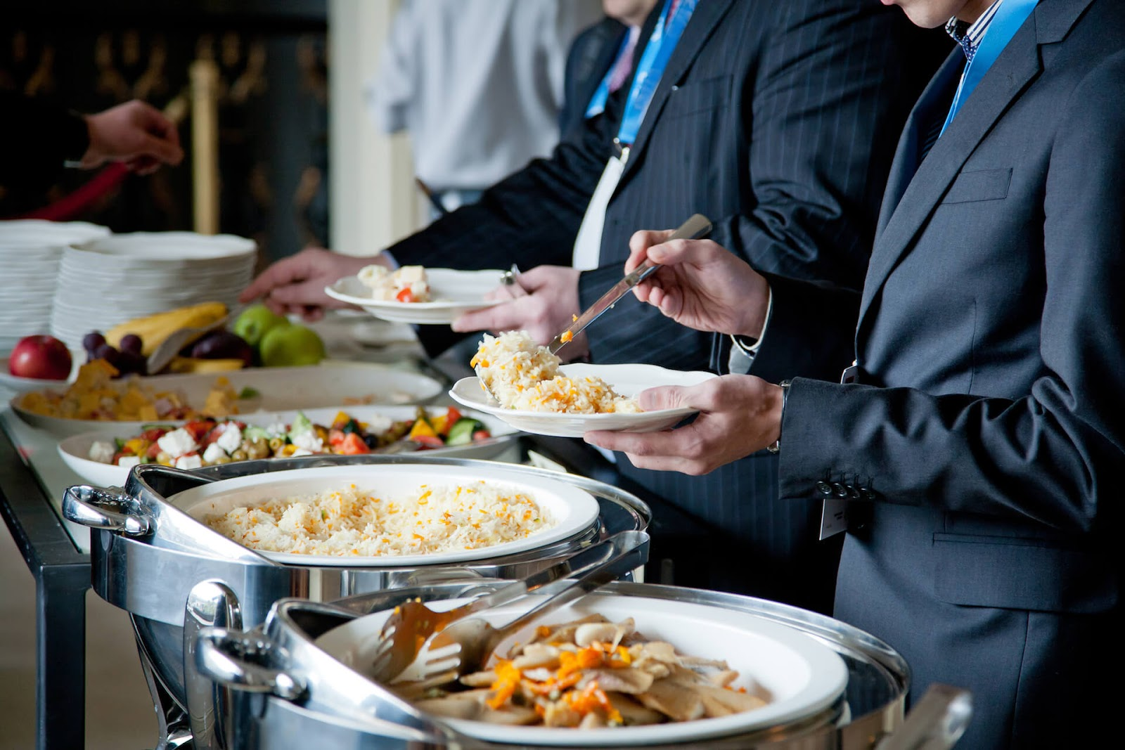 Men in suits moving through a buffet