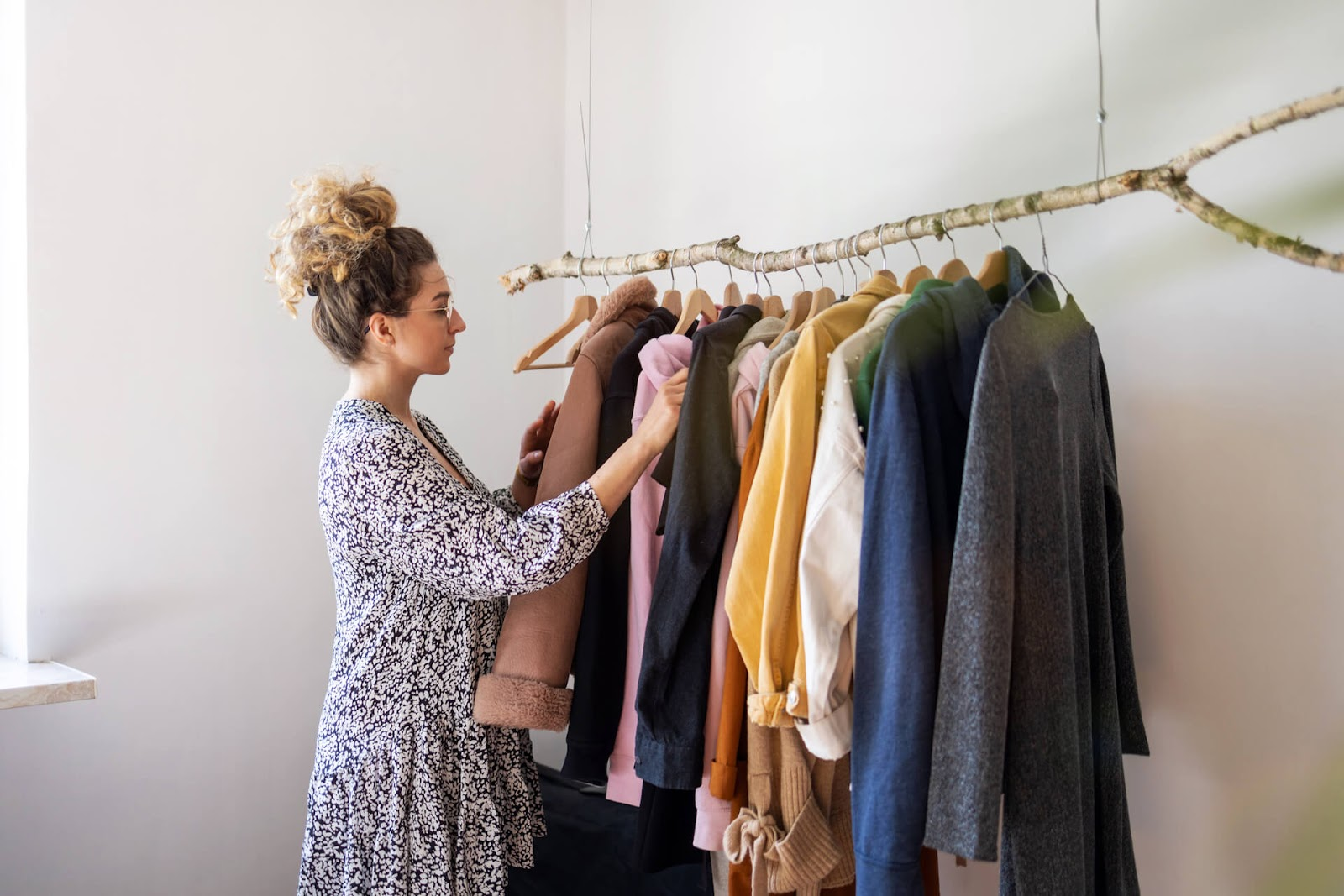Woman picking clothes from her hip, tree branch clothing rack