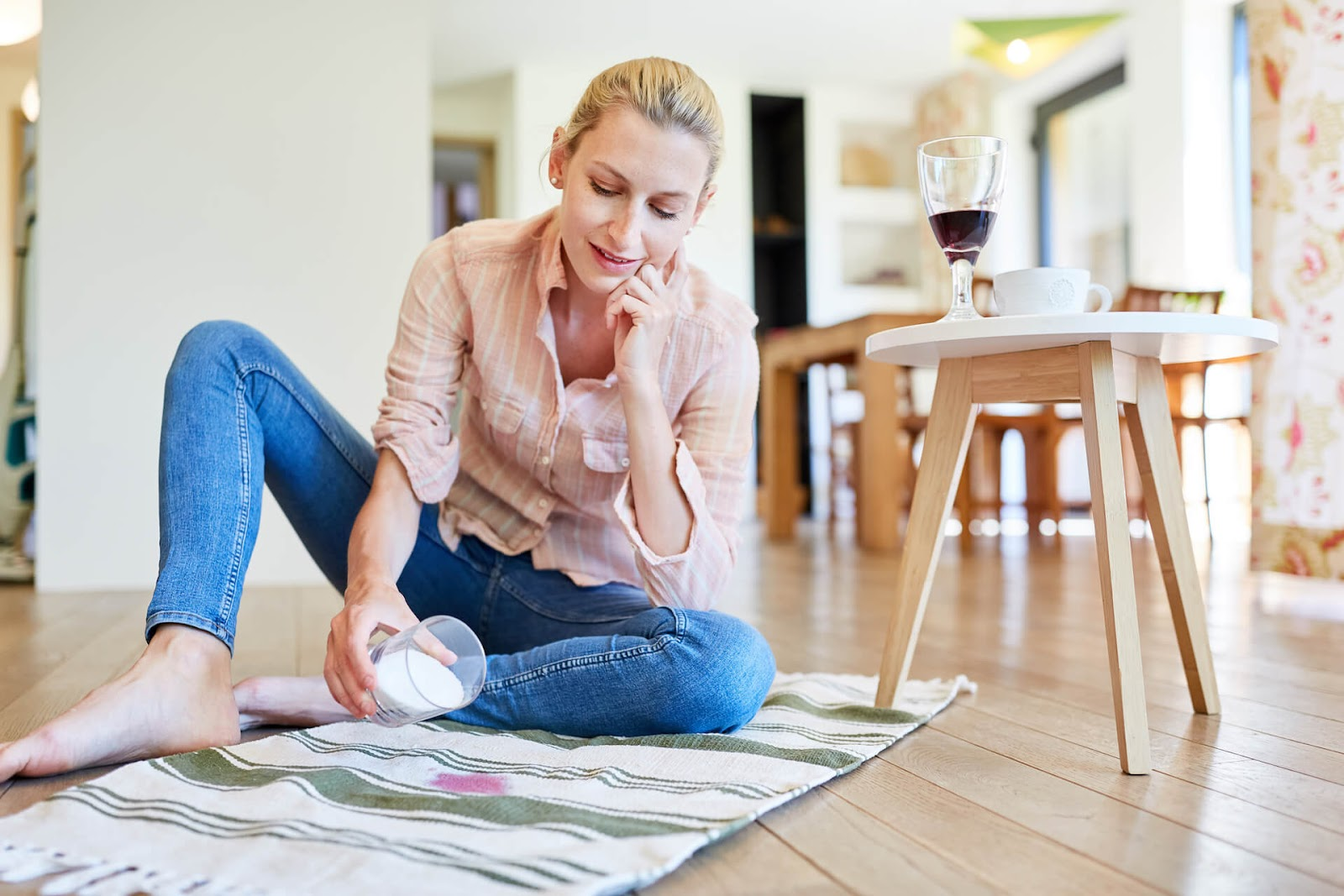 Woman cleaning up red wine stain from carpet
