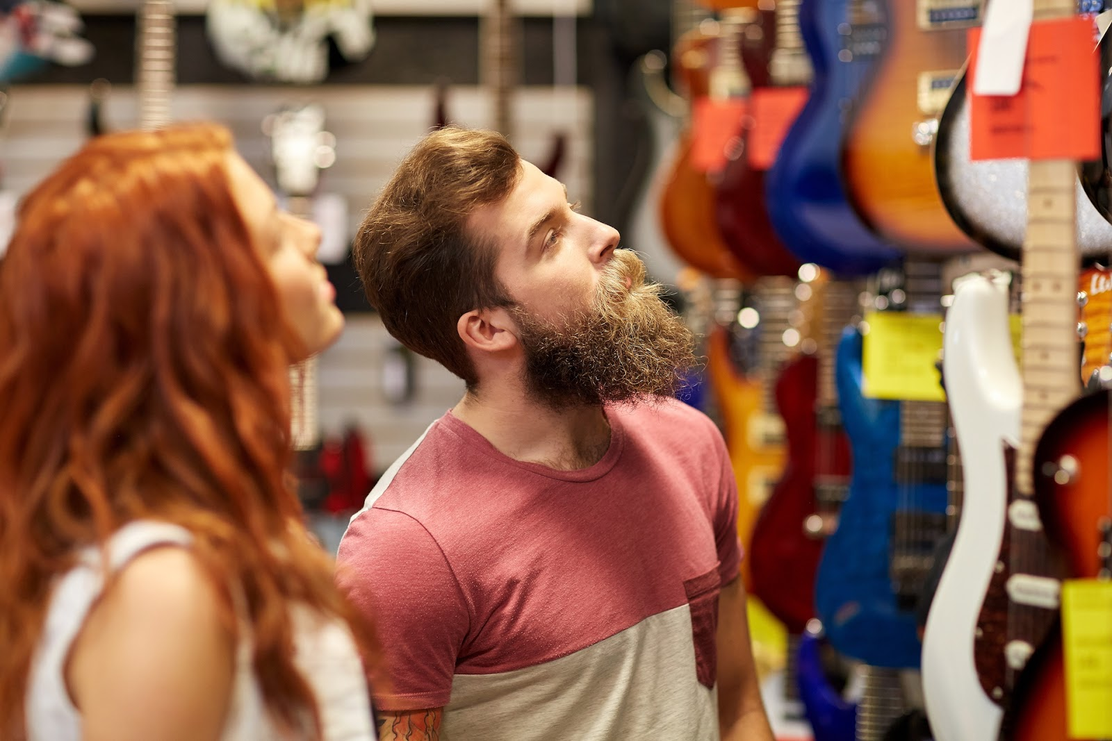 Bearded man and woman looking at guitars in the store