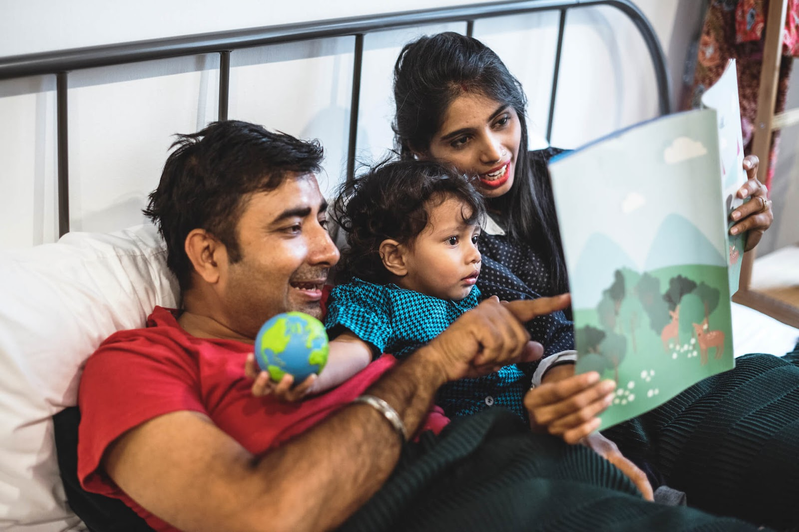 Mom and dad reading to toddler in bed